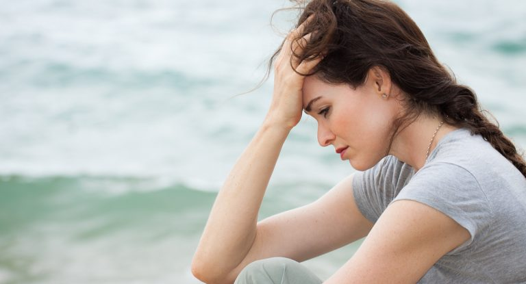 recovering addict on the beach going through emotional relapse