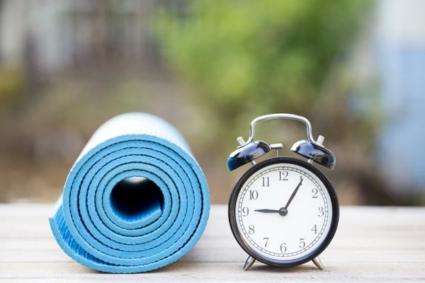 Yoga mat rolled up and alarm clock