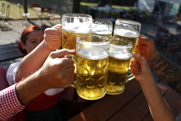 Group of people lifting filled beer mugs as a toast.