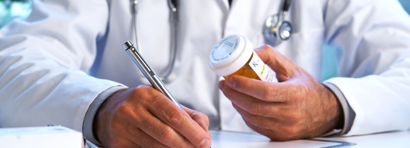 Doctor writing on a prescription holding a pill bottle.