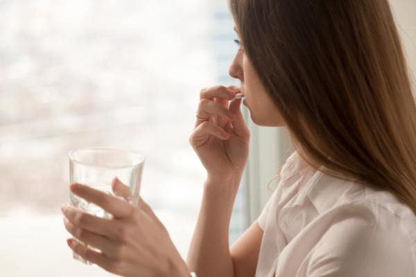 Woman taking a pill with a glass of water.