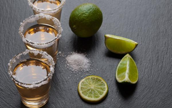 Glasses of alcohol with limes and salt on a table top.