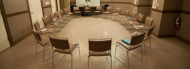 Empty room with chairs placed in a large circle.