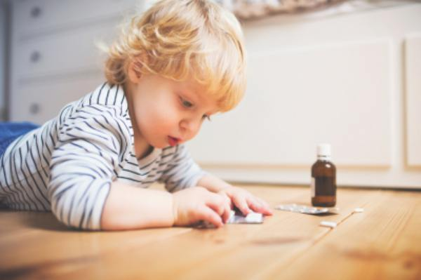 Child lying on the floor with a pill packet.