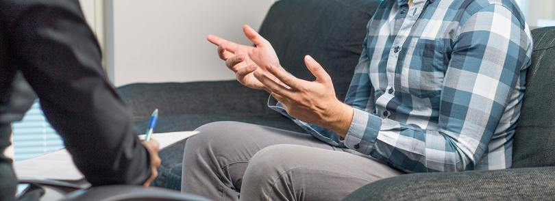 Person sitting on a couch with a therapist opposite them.