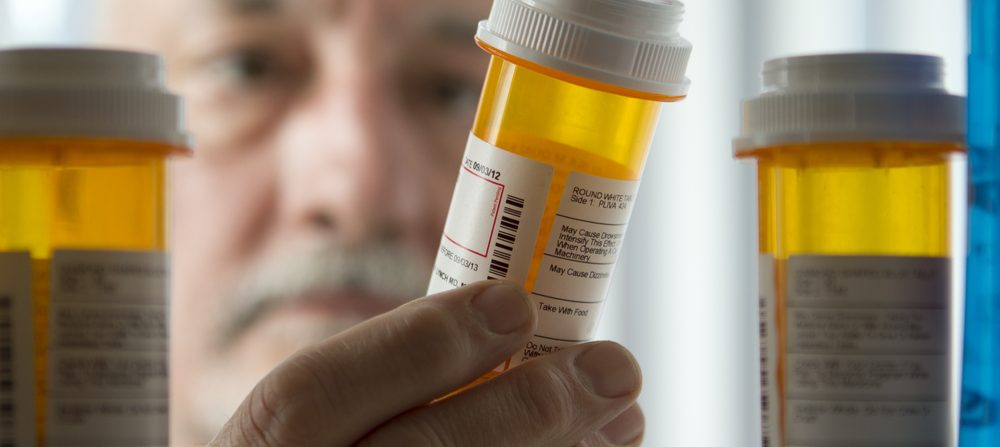 A man reads the label on a prescription pill bottle.