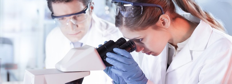 A woman in a lab coat looks into a microscope.