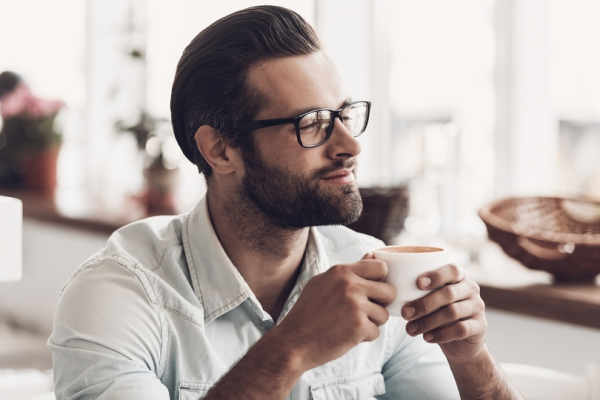 A man wearing glasses drinking coffee