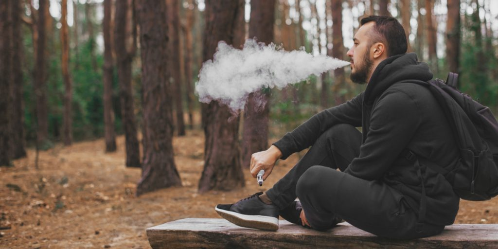 A male high school student vaping in the woods during the school day