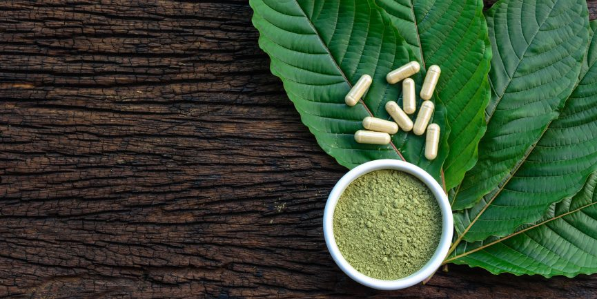Kratom leaves, pills, and powder sitting on top of a wood table