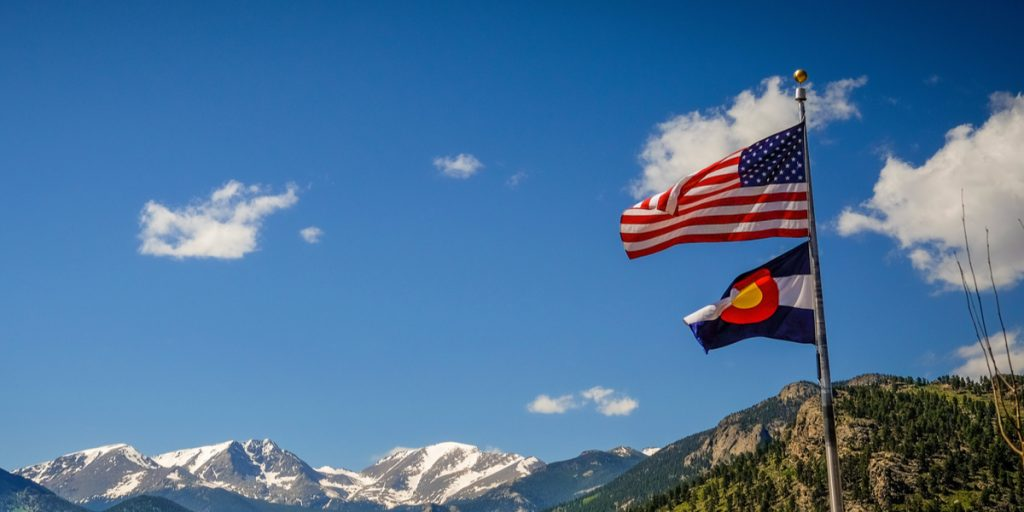 Two raised flags blowing in the wind in the colorado mountains