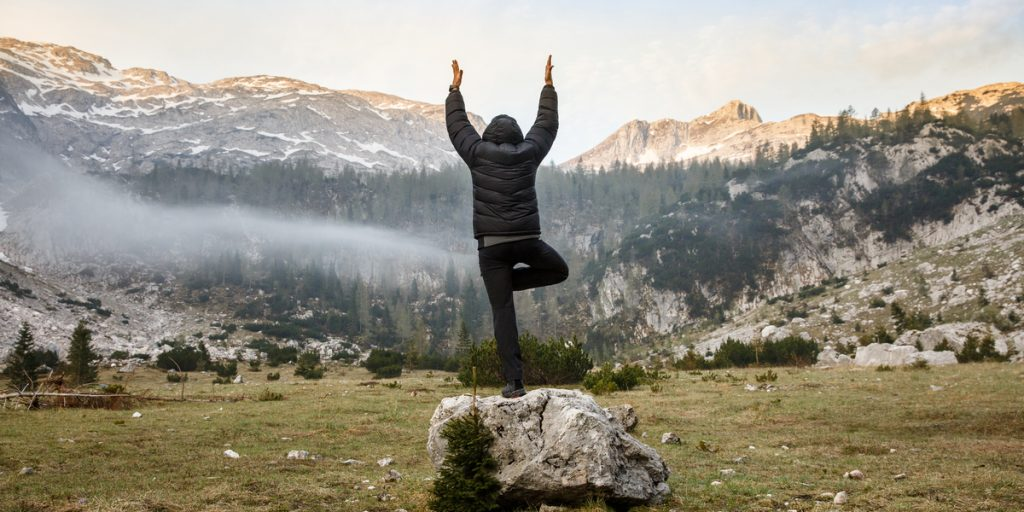 Person practicing yoga on a rock overlooking mountains trying to destress