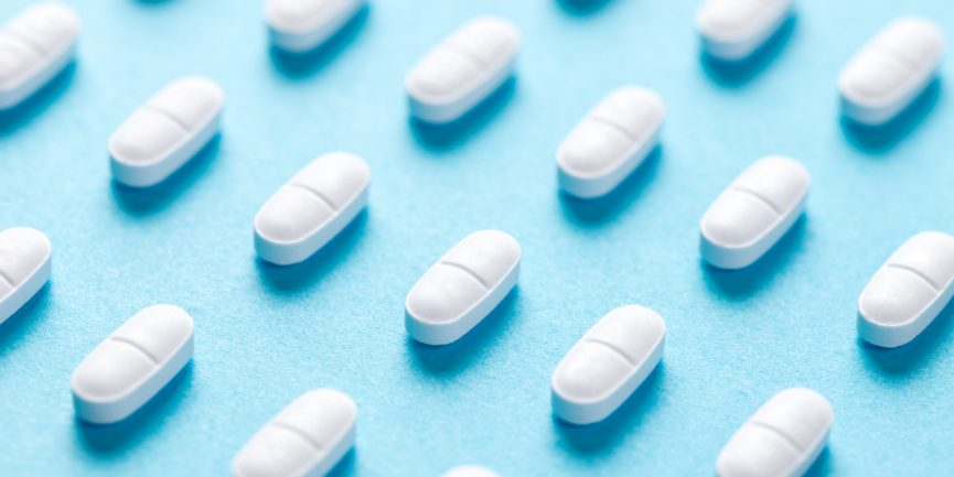 white prescription pills lined up in rows