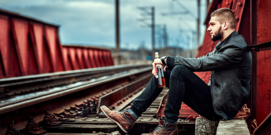 Young person sitting on railroad tracks with a bottle of whiskey, looking sad