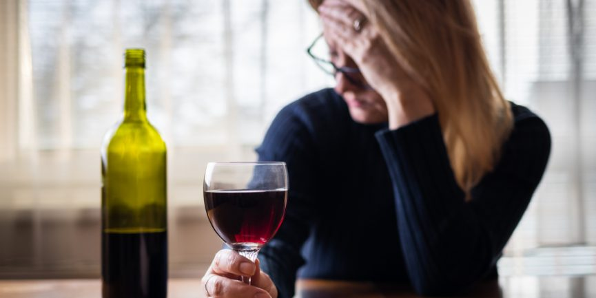 woman suffering from anxiety self medicating with a glass of wine